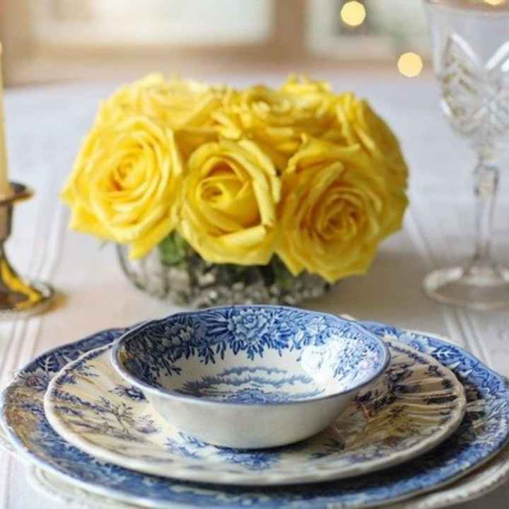 traditional table setting with blue transferware, crystal goblets and yellow rose centerpiece