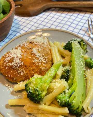 pasta and broccoli with light olive oil, garlic, and parmesan cheese dressing on plate with parmesan chicken