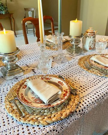 Table set with place settings, flatware, and glasses for a holiday meal