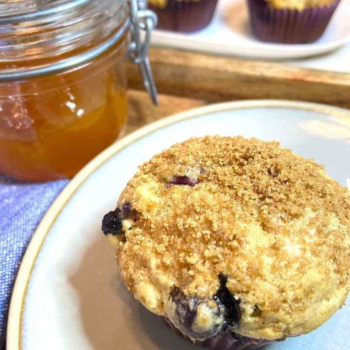blueberry muffin on plate with jar of jelly