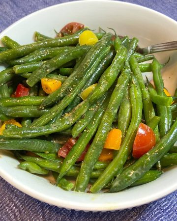 prepared green beans and tomatoes in bowl ready to serve