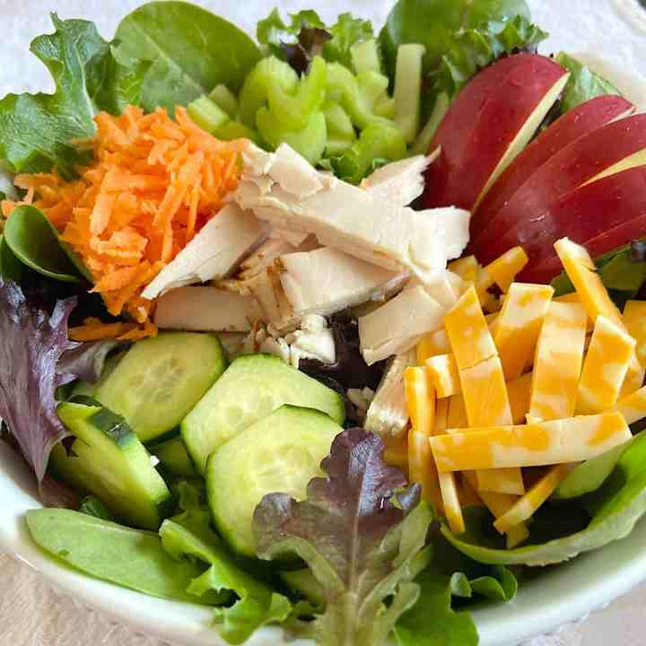 bowl of salad with greens, chopped vegetables, fruit, turkey, and cheese.