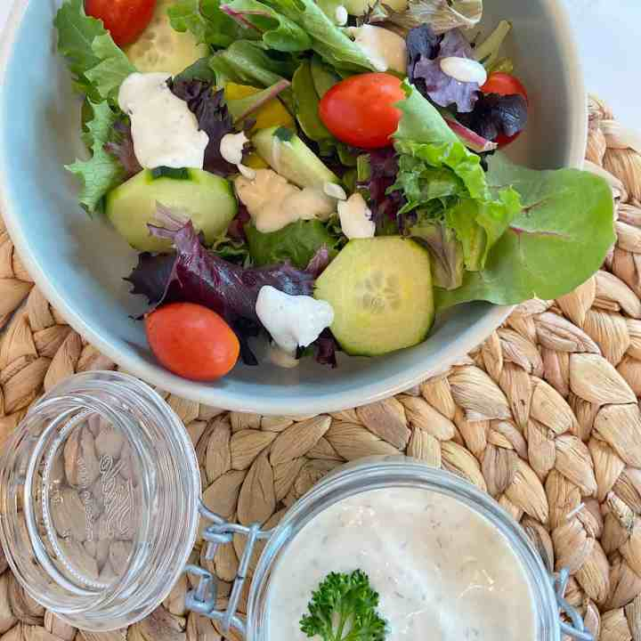 homemade ranch dressing in a jar with bowl of salad