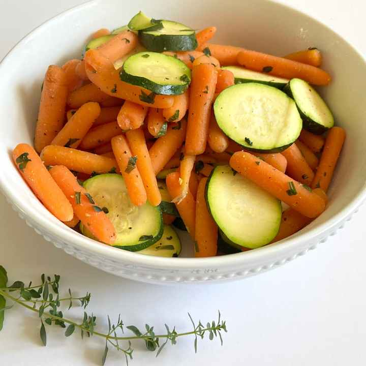 bowl of baby carrots and zucchini seasoned with spices and broth
