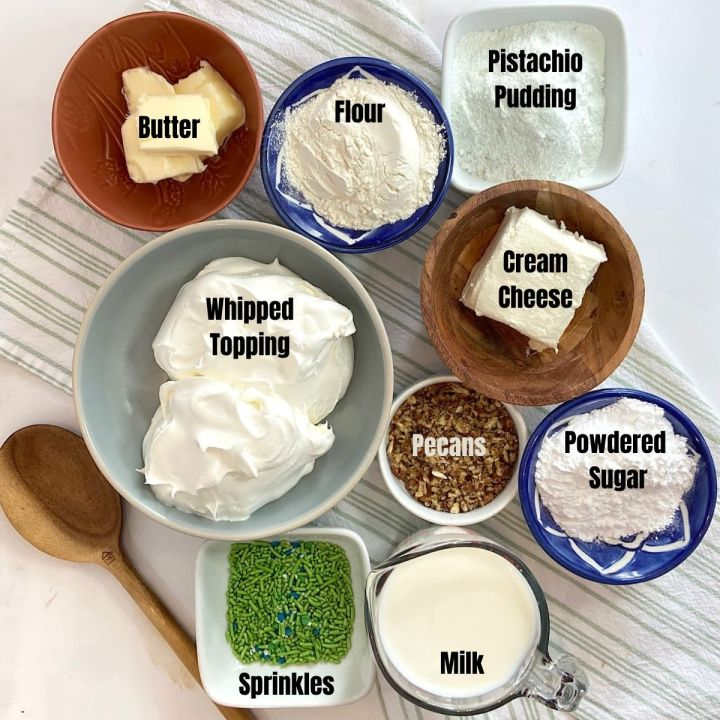 measured ingredients of butter, flour, pudding, whipped topping, cream cheese, pecans powdered sugar, milk, and sprinkle