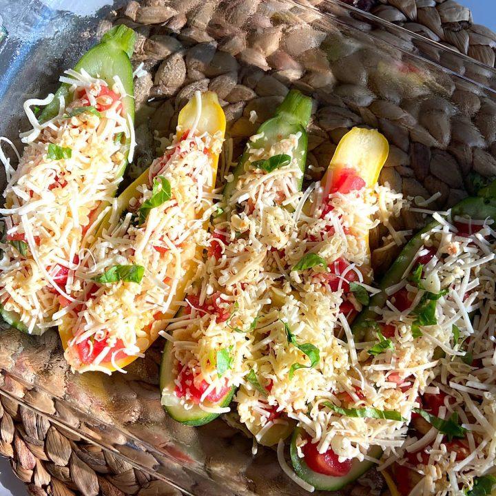 Stuffed zucchini and squash halves in baking dish.