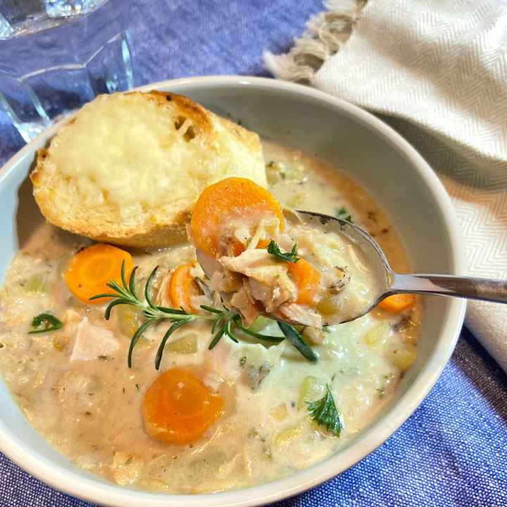 a spoonful of turkey wild rice soup in bowl with slice of cheese bread