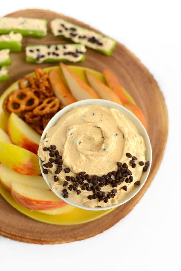 peanut butter greek yogurt dip with fruit and pretzels ready for dipping