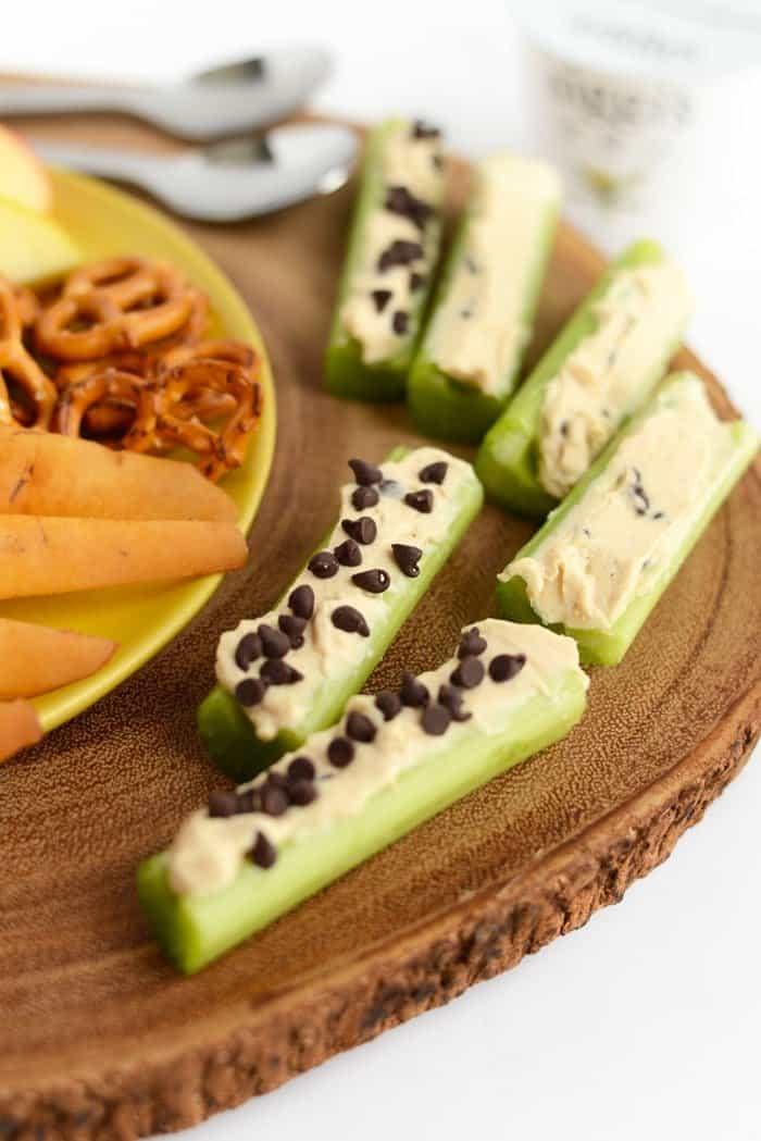 peanut butter greek yogurt dip spread in celery slices for ants on a log