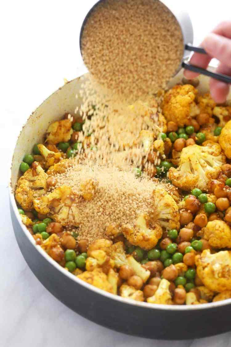 couscous being poured over the rest of the moroccan chickpea ingredients in a skillet