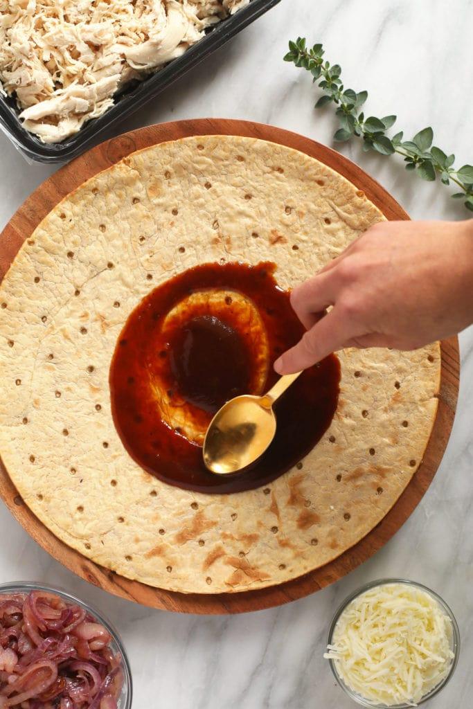 spreading bbq sauce on pizza crust