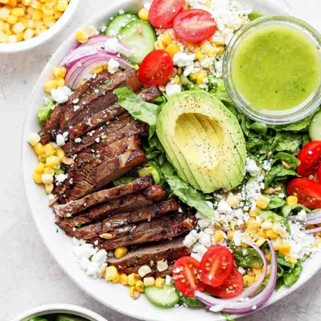 steak salad in bowl with dressing