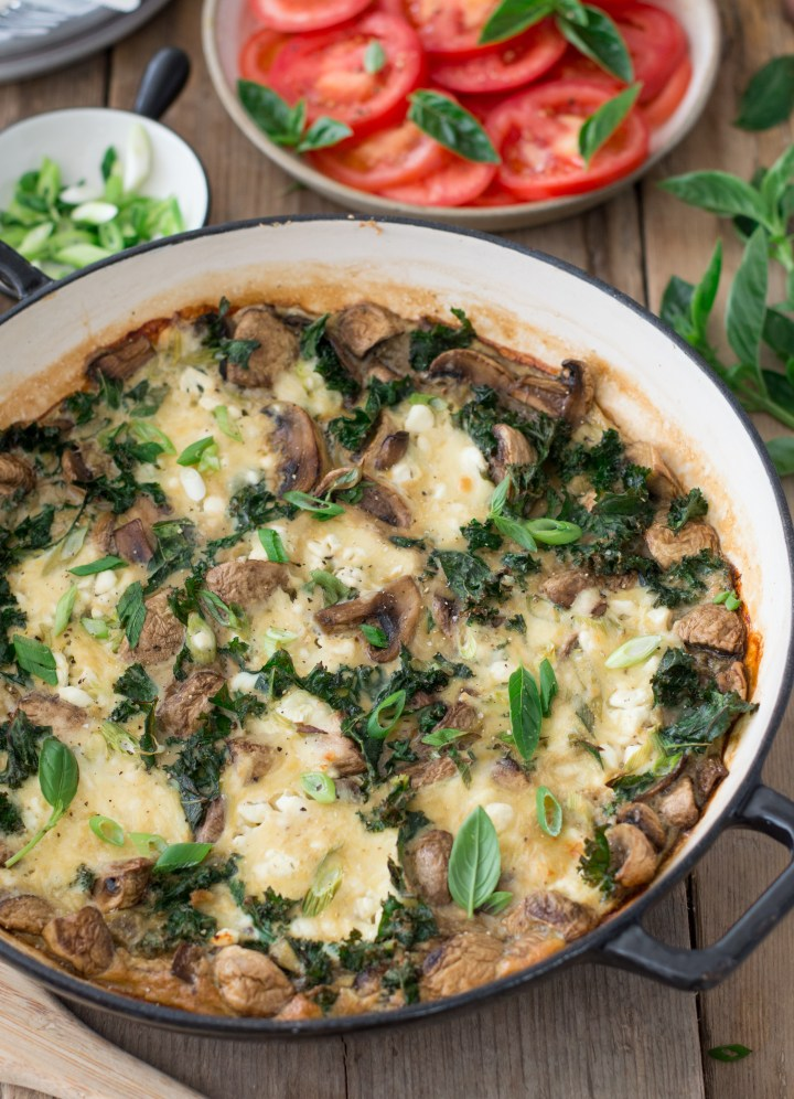Kale & mushroom frittata in a pan with sliced tomatoes on the side