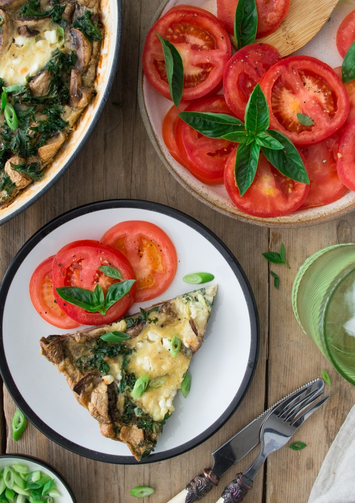 A slice of Mushroom and kale frittata slice with fresh tomatoes on the side