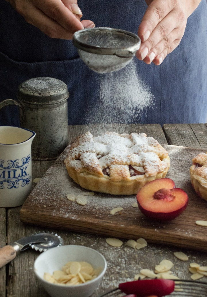 Plum pie with person behind it sifting the flour