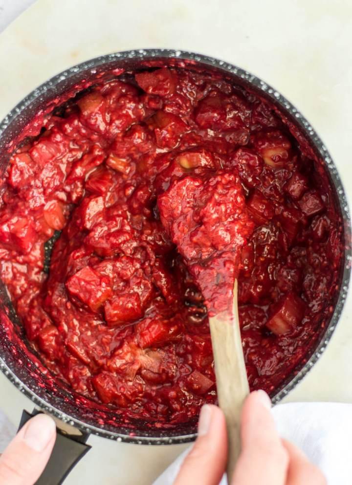 Stewed raspberries and rhubarb in a black saucepan