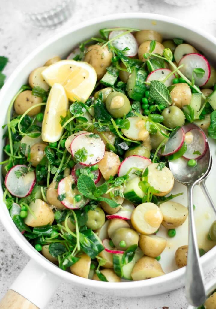 Vegan potato salad in a white bowl, top down close up view