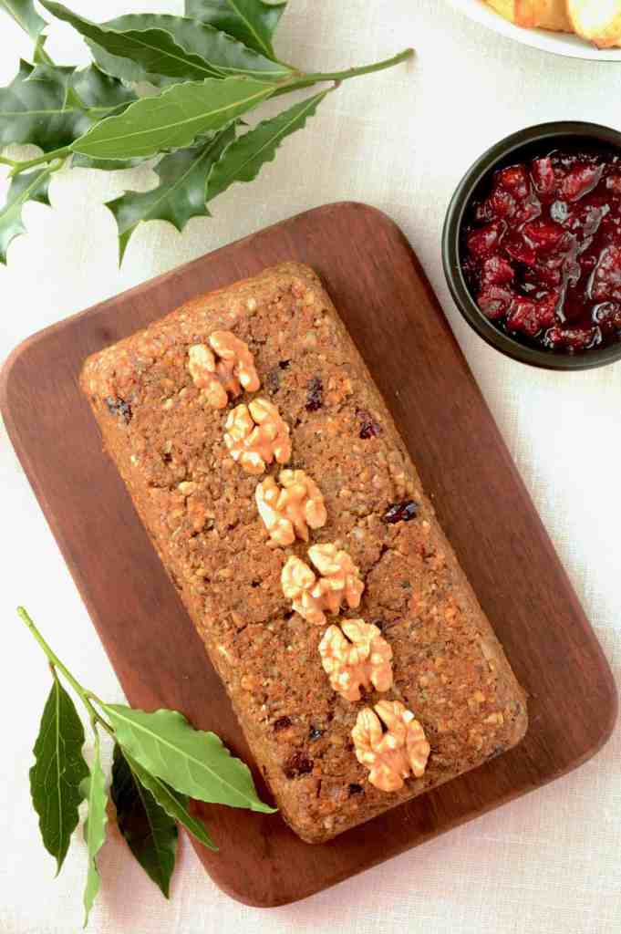 Top down view of vegan nut roast loaf decorated with walnuts on a wooden board, cranberry sauce on side