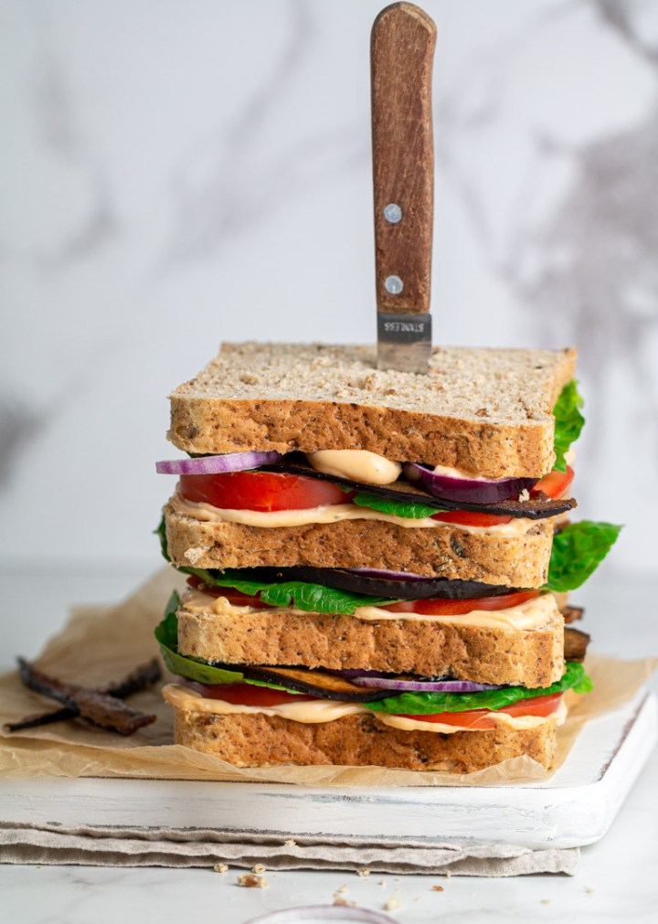 Vegan BLT sandwich with eggplant bacon on a white board, knife in the sandwich