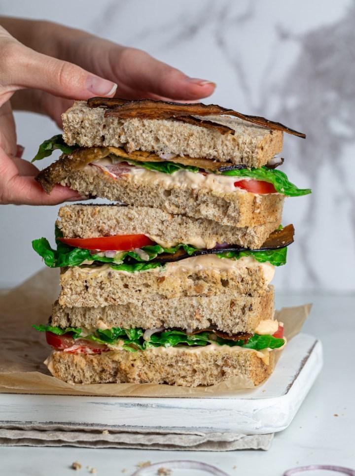 Hands holding a vegan BLT sandwich