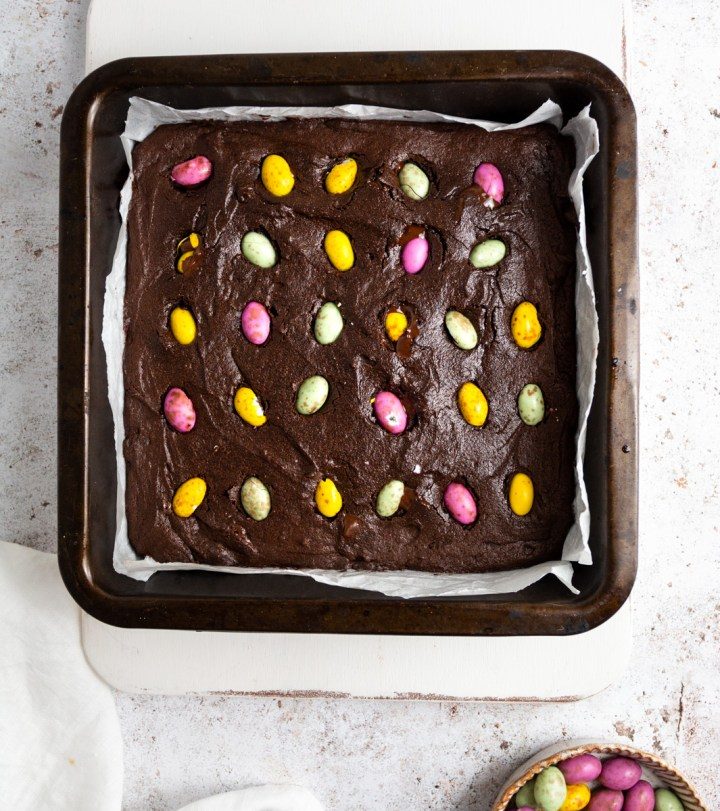Top down view of vegan brownies in a pan with mini chocolate eggs