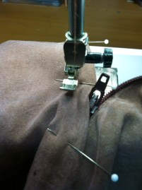 Drop the needle and raise the presser foot to zip the zipper so you can complete the stitching.
