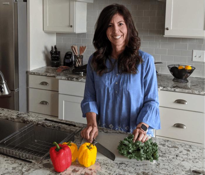 Stephanie cutting vegetables in kitchen