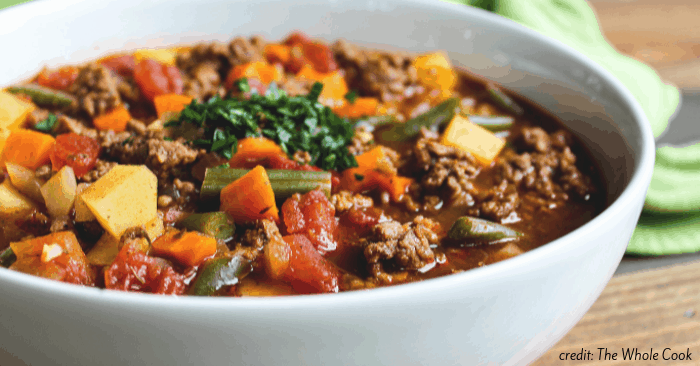 a white bowl of ground beef soup with vegetables