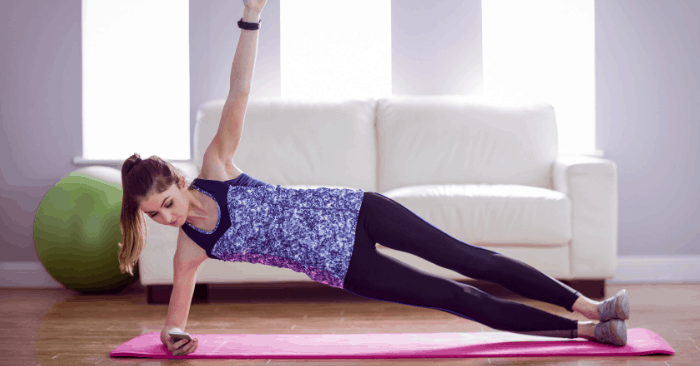 woman at home toning muscles with planks