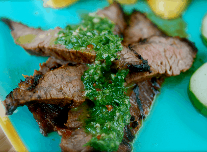 sliced flank steak with chimichurri sauce on plate