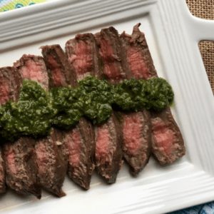 flank steak with chimichurri on a plate