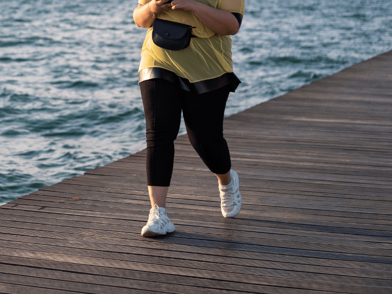 overweight lady walking by water on pier