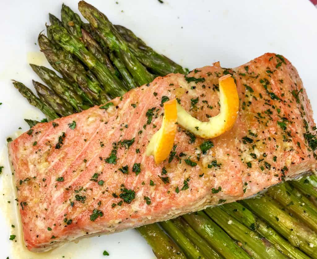 orange glazed salmon over asparagus on a white plate