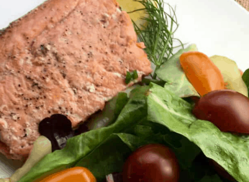 salmon with dill and salad on a white plate