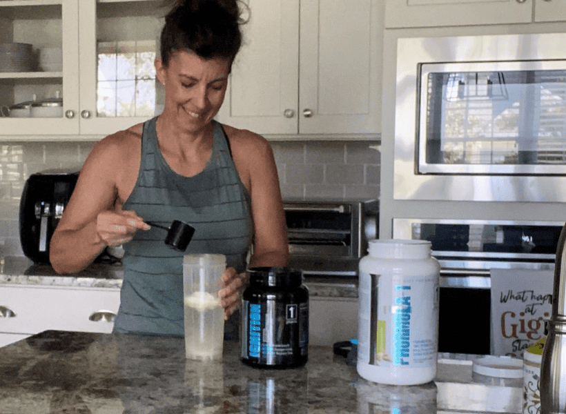 woman mixing post workout protein shake in kitchen
