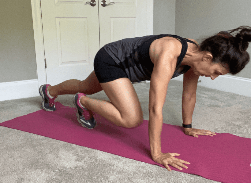 woman doing bodyweight exercises on pink yoga mat