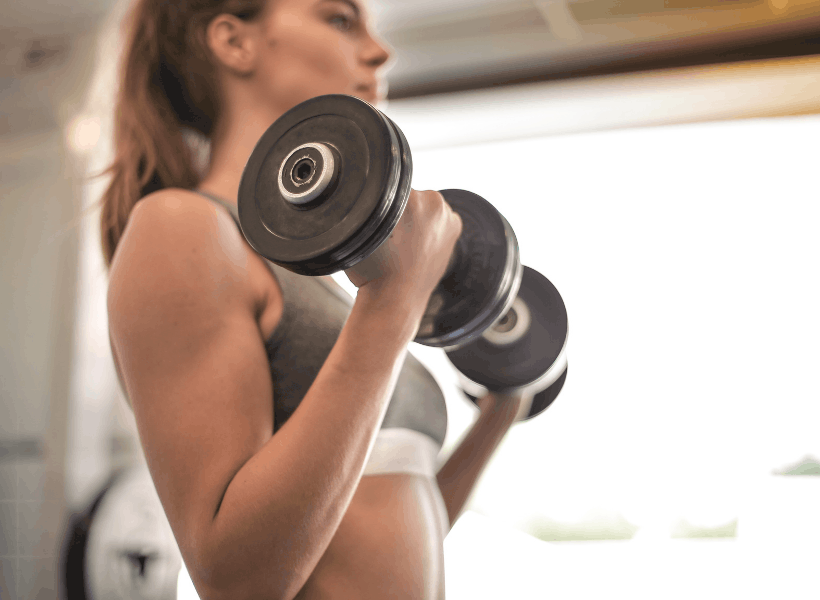woman lifting dumbbells doing bicep exercises