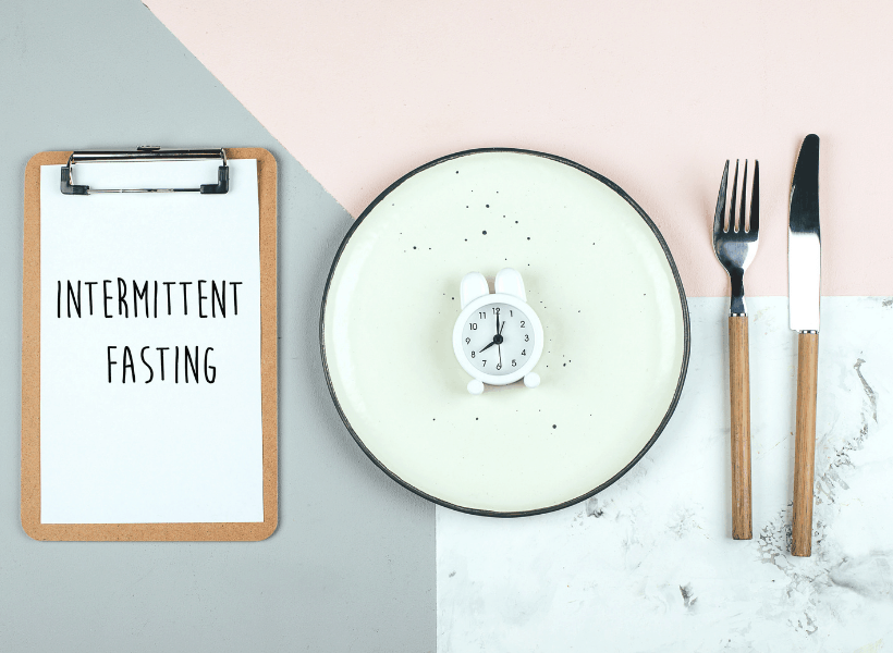 clipboard with white sheet that says intermittent fasting beside a green plate with a clock beside a fork and knife