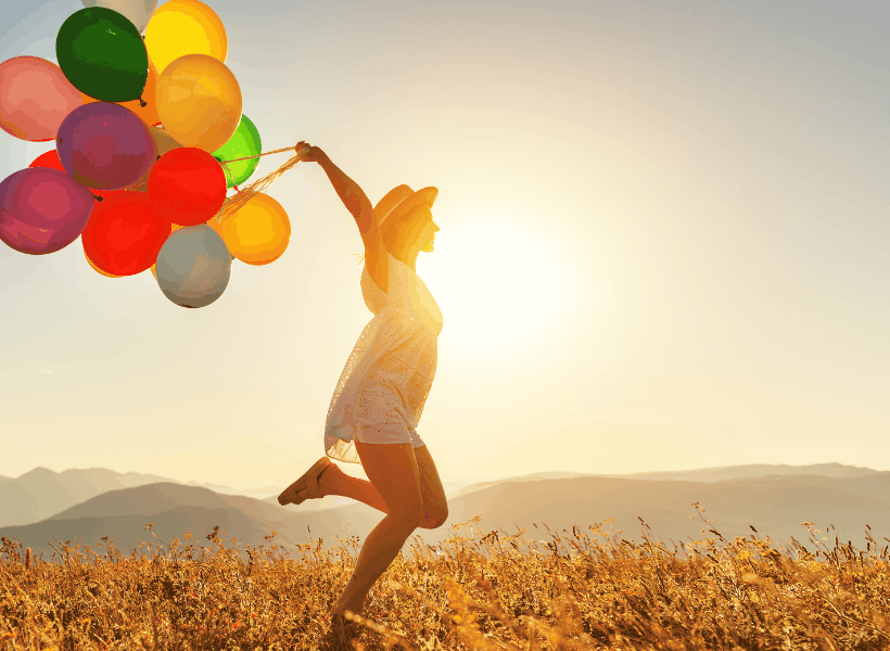 woman holding a dozen or so multicolored balloons walking in meadow with sun in background