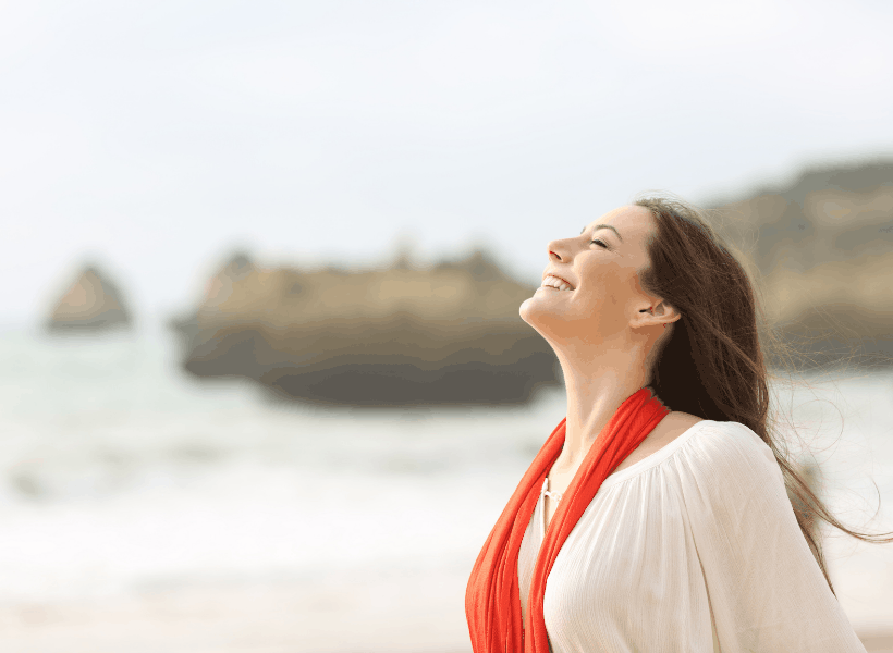woman with face up towards sky smiling while standing on the beach