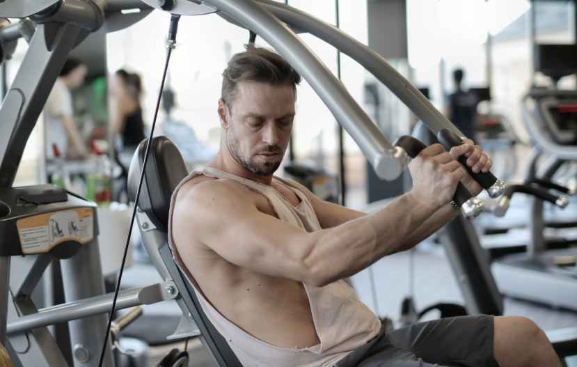 fit male bodybuilder exercising with metal machine in gym