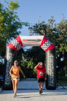 Man and woman running across finish line