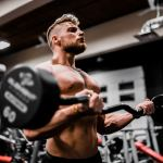 Young man doing bicep curls with an EZ bar