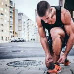 A lean man is tying his shoes, getting ready to run. He knows his BMR and knows that with his current diet, he'll need to add cardio to not gain weight.