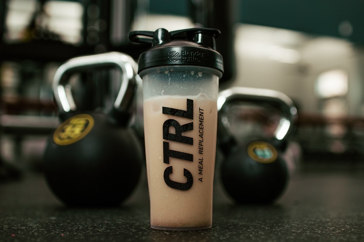 A protein shake is placed in front of two kettlebells. The photograph wonders if he should drink his protein shake after or before his workout