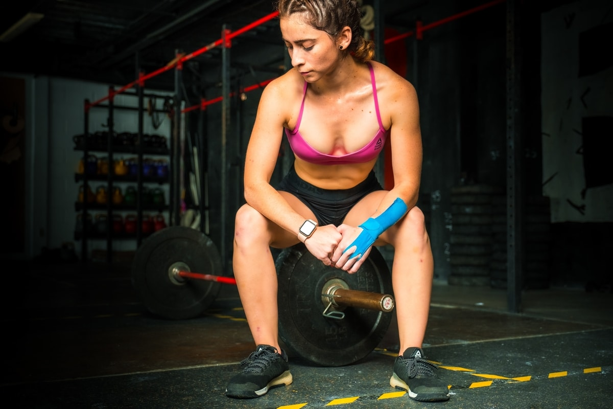 """A woman is sitting on a weight attached to a barbell. She's in-between sets and her mind drifts."""" What is water retention, really?"""" She wonders while waiting for her next set."""
