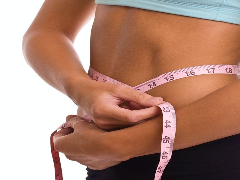 A woman is measuring her waist with a tape measure.