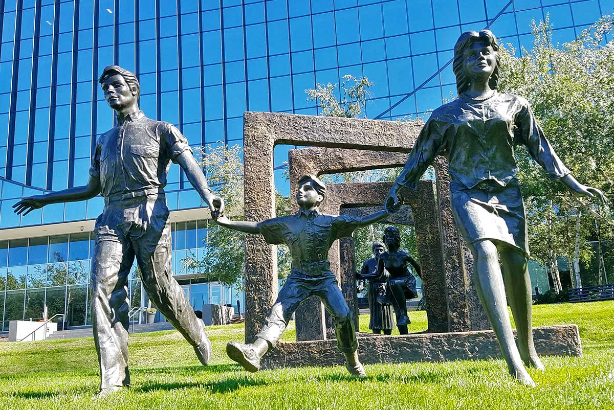 Statue of family skipping through grass field