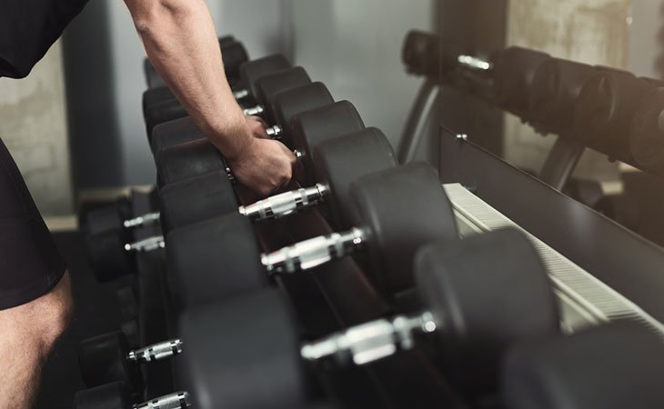 Man Picking Dumbbell From Weight Rack