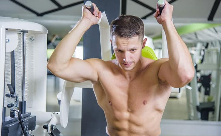 Fitness Man Working Out Using Shoulder Press Machine